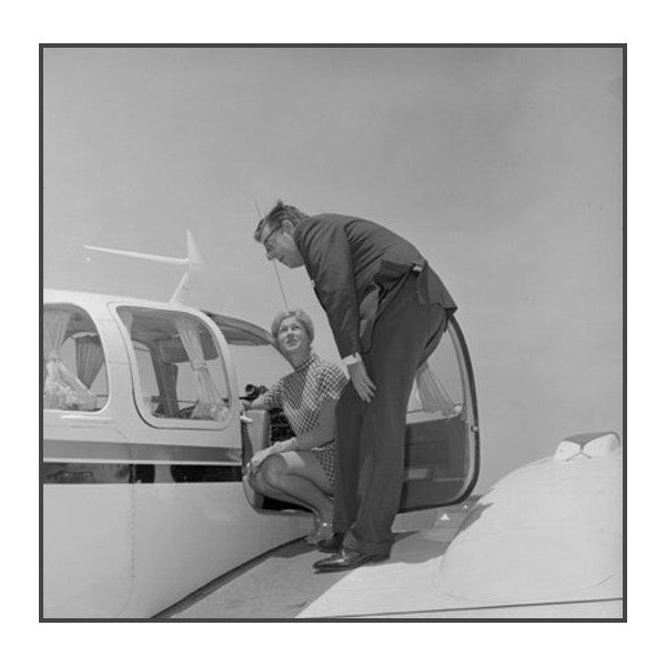 Robin Miller and man standing on wing of aircraft inspecting cockpit. 1969