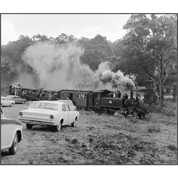 Cars wait at rail crossing for Puffing Billy to pass 1968