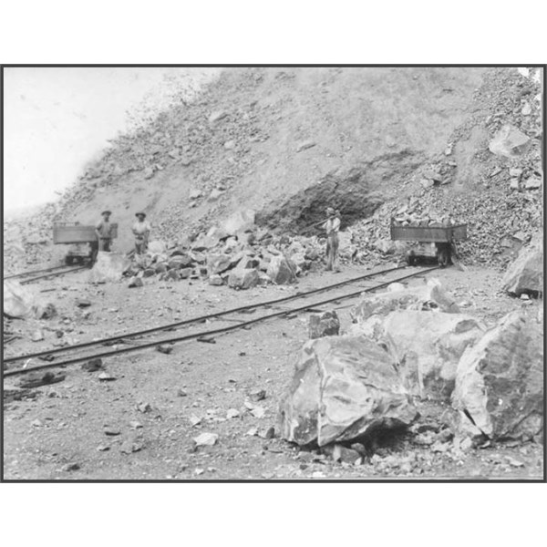 Quarrymen breaking and loading stone into skips c1920