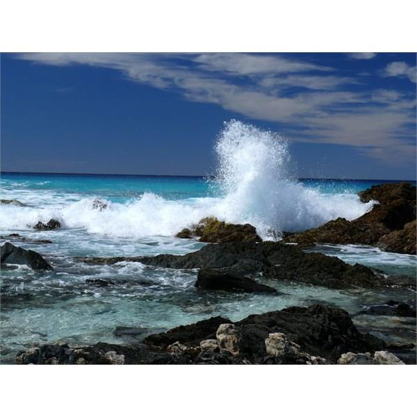 Watching a storm swell crash onto rocks