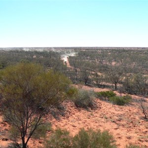 Vehicles leave dust through the Finke floodout